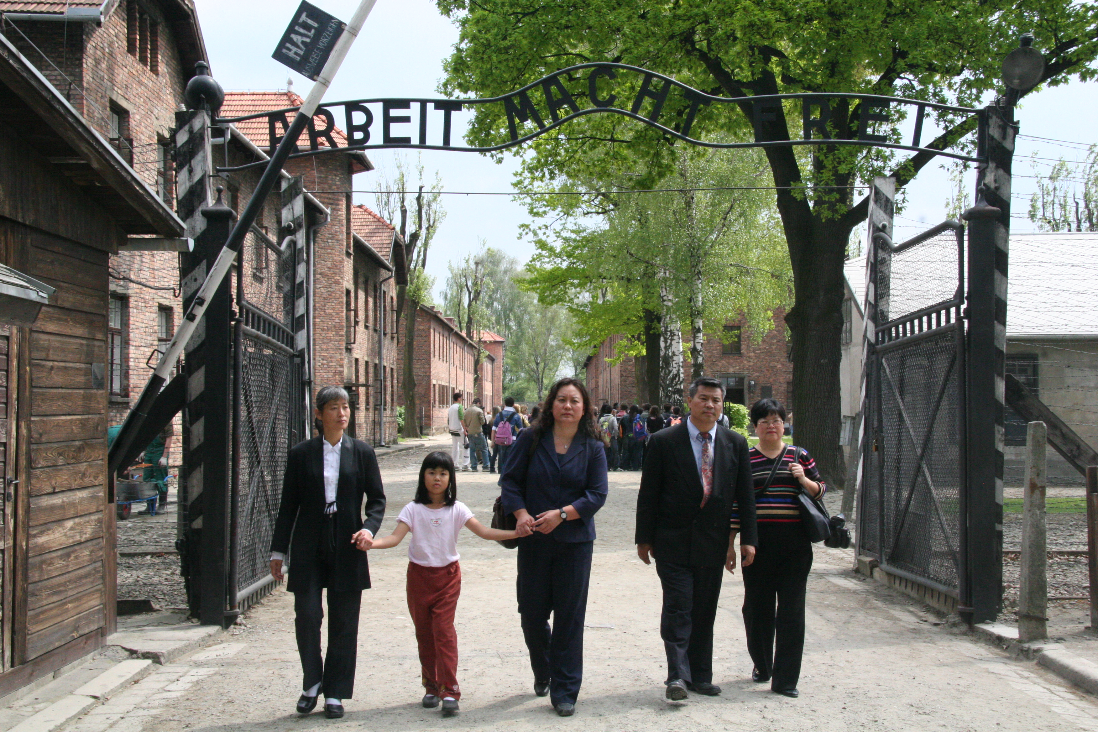 "NEVER AGAIN: The Chinese panelists at the ""Never Again: Appeal to the World"" forum on organ harvesting death camps in China walk through the infamous ""Work Shall Set You Free"" gate at the Auschwitz-Birkenau Memorial and Museum, on May 9, 2006. (Jan Jekielek/The Epoch Times)"