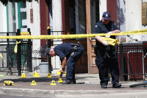 Authorities retrieve evidence markers at the scene of a mass shooting in Ohio