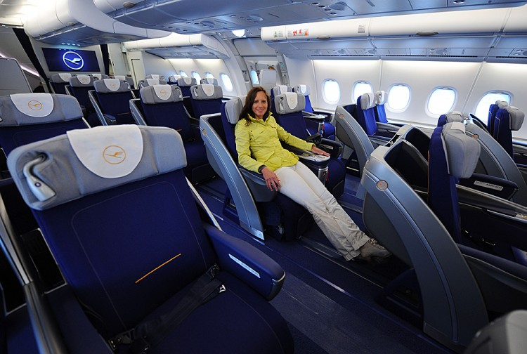A young woman poses in a business class seat of the new airplane Airbus A380