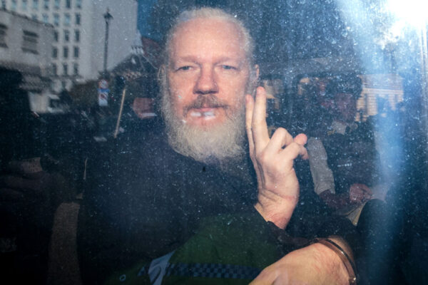 Julian Assange gestures to the media