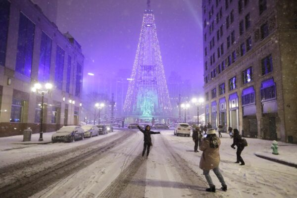 People pose for photos as snow falls
