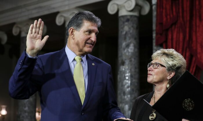 Sen. Joe Manchin (D-WV.) is flanked his wife Gayle as he is sworn in by Vice President Mike Pence (out of frame) during the swearing-in re-enactments for recently elected senators in the Old Senate Chamber on Capitol Hill in Washington, on Jan. 3, 2019. (Alex Edelman/AFP via Getty Images)