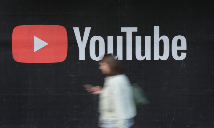 A woman with a smartphone walks past a billboard advertisement for YouTube in Berlin on Sept. 27, 2019. (Sean Gallup/Getty Images)