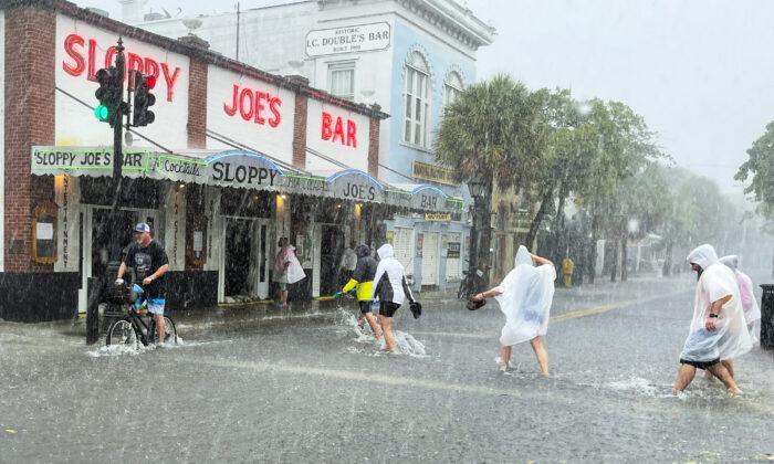 Determined visitors head for Sloppy Joe's Bar while crossing a flooded Duval Street as heavy winds and rain pass over Key West, Fla., on July 6, 2021. (Rob O'Neal/The Key West Citizen via AP)